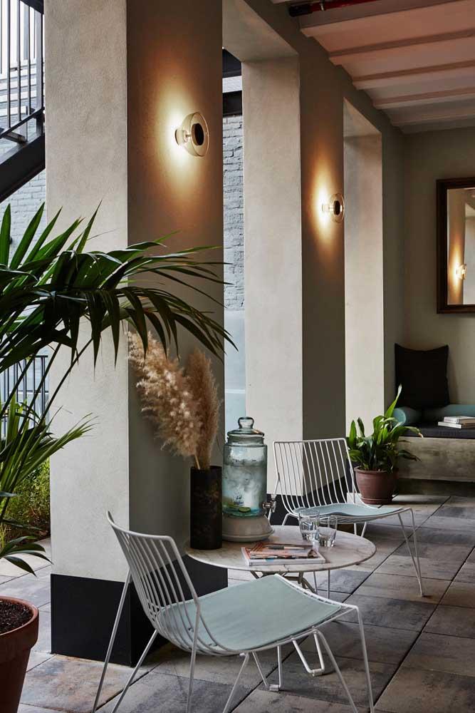 Arandelas externas em vidro para espaço coberto da varanda da casa; peças em vidro também são indicadas para propagar melhor a luz