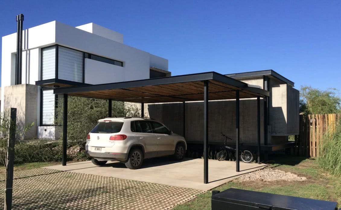 A concregrama no acesso determina o paisagismo dessa casa, e para não fugir da proposta a escolha foi por utilizar placas de concreto na garagem
