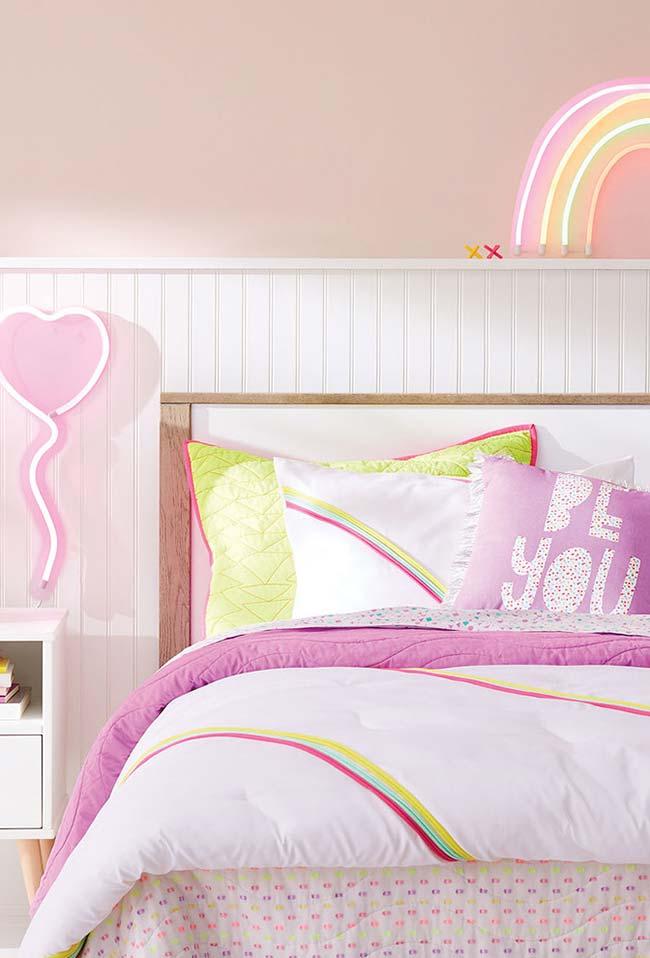 Quarto de menina jovial com um toque de Neon arco-íris sobre a cama