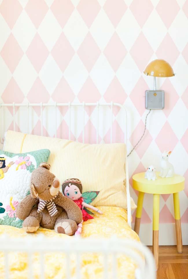 Quarto de menina com papel de parede rosa e branco com formas geométricas.