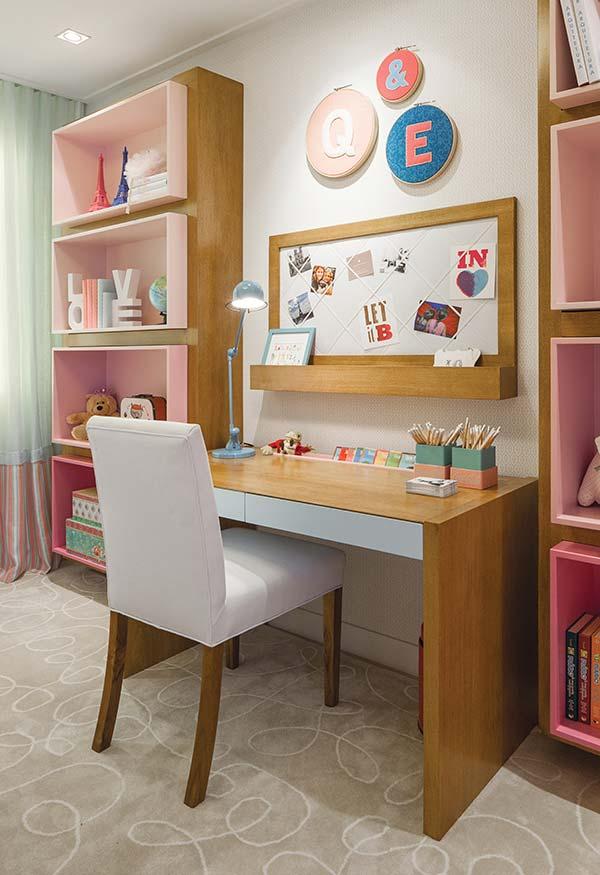 Decoração de quarto de menina com escrivaninha e prateleiras rosas