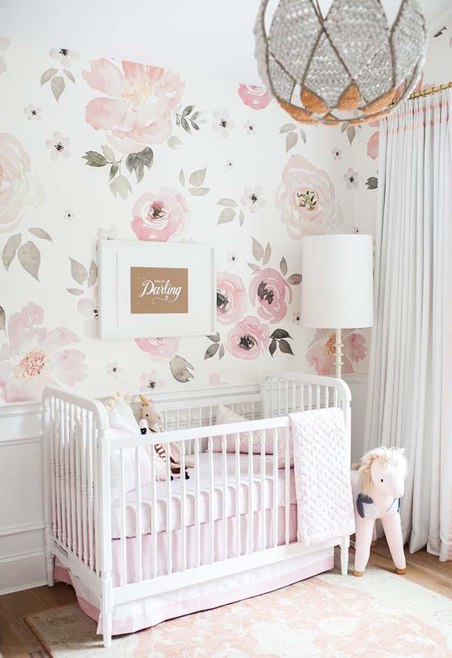 Quarto de bebê de tons claros apostou em um papel de parede com flores gigantes