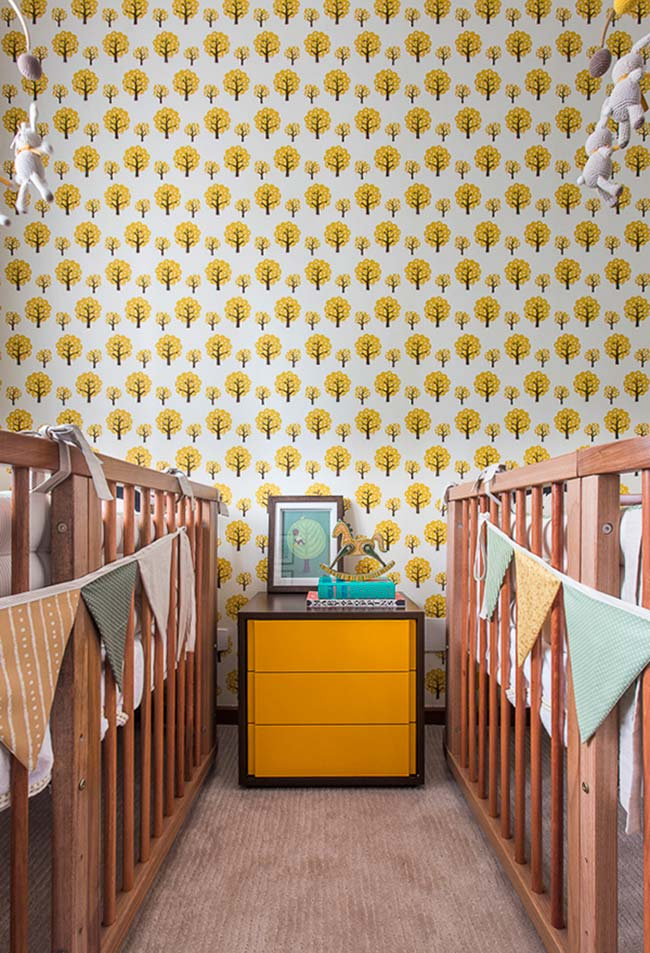 Quartinho com bercinhos de madeira em dose dupla usa papel de parede de fundo claro e estampa de árvores amarelas