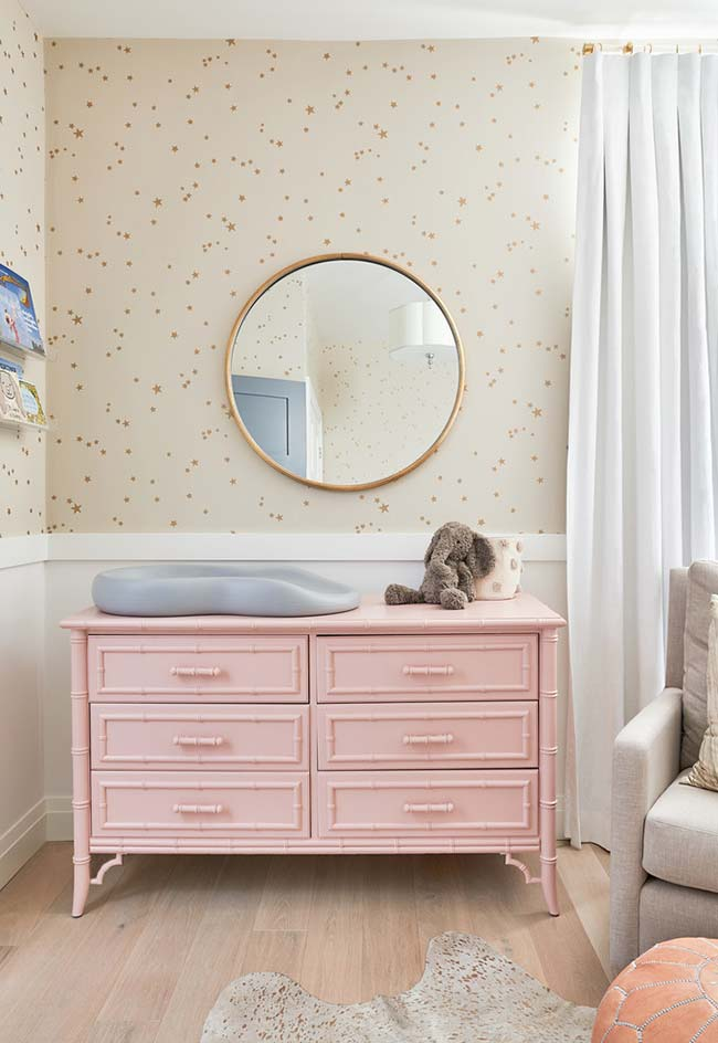 Nessa outra imagem, o papel de parede se harmoniza com o espelho redondo com moldura dourada e a mobília rosa clara