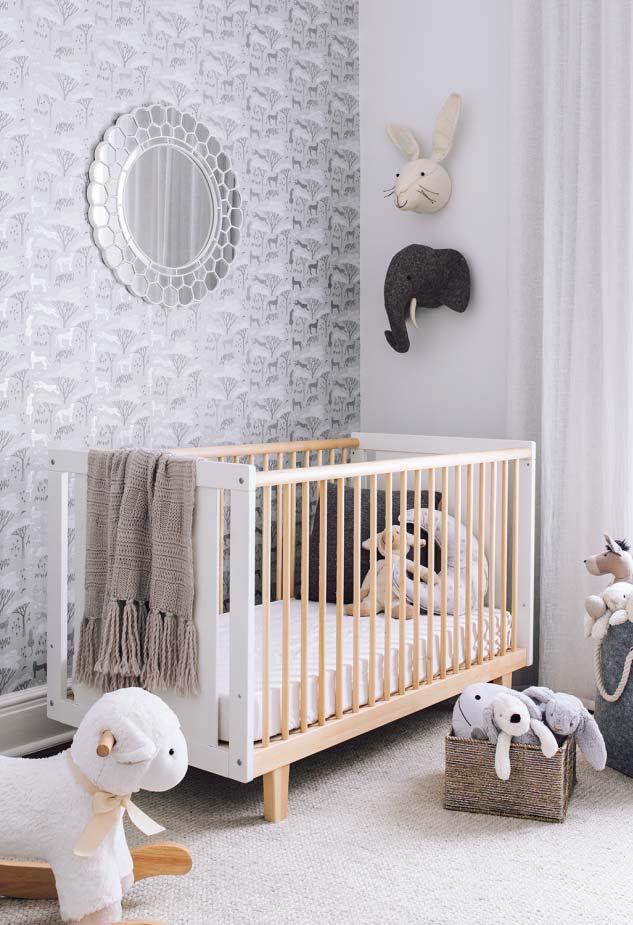 Nesse quarto de bebê, o espelho redondo se harmoniza com o papel de parede branco, preto e cinza