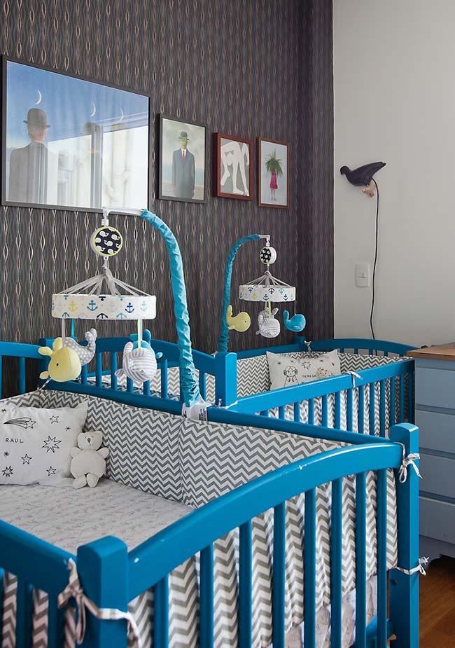 O quarto para gêmeos ganhou uma decoração forte e marcante com o papel de parede preto e os berços azul turquesa