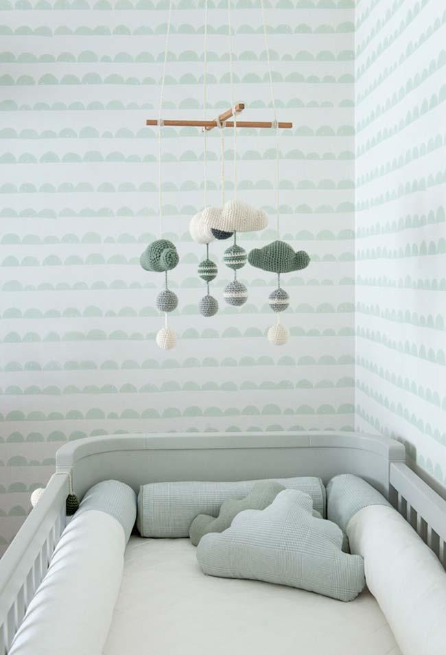 Papel de parede de estampa delicada em tons de verde e branco contorna todo o quarto do bebê