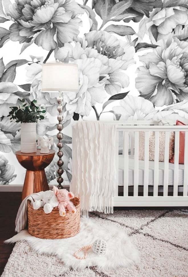 Quarto de bebê elegantemente decorado com flores em preto e branco de tamanho gigante