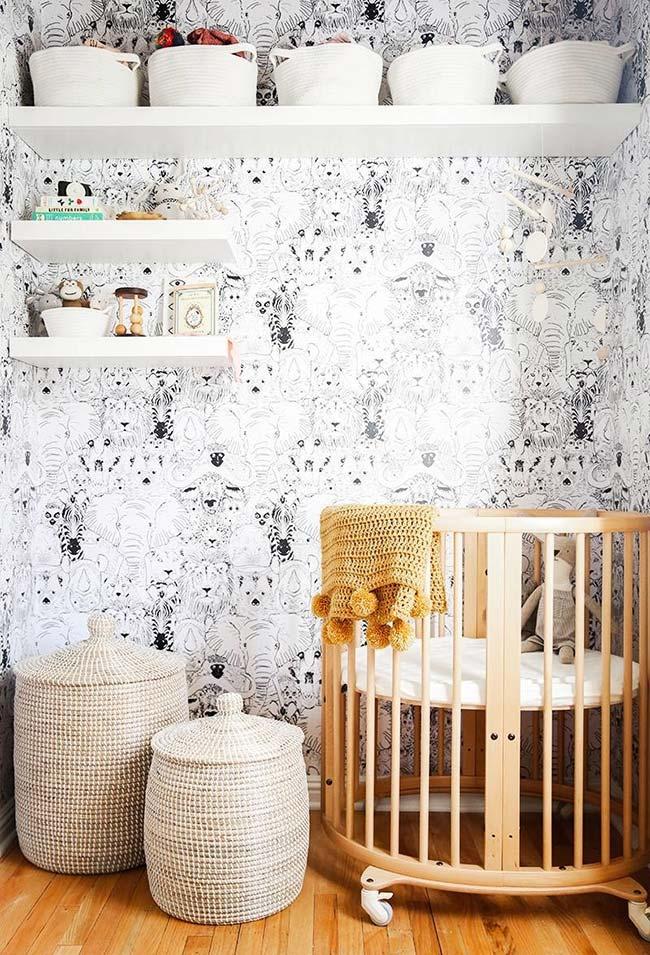 Nesse quarto de bebê, o papel de parede foi complementado com a presença das prateleiras brancas