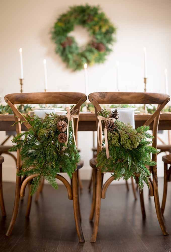 Um arranjo com flores preso nas cadeiras dá um toque diferenciado na decoração da mesa de natal