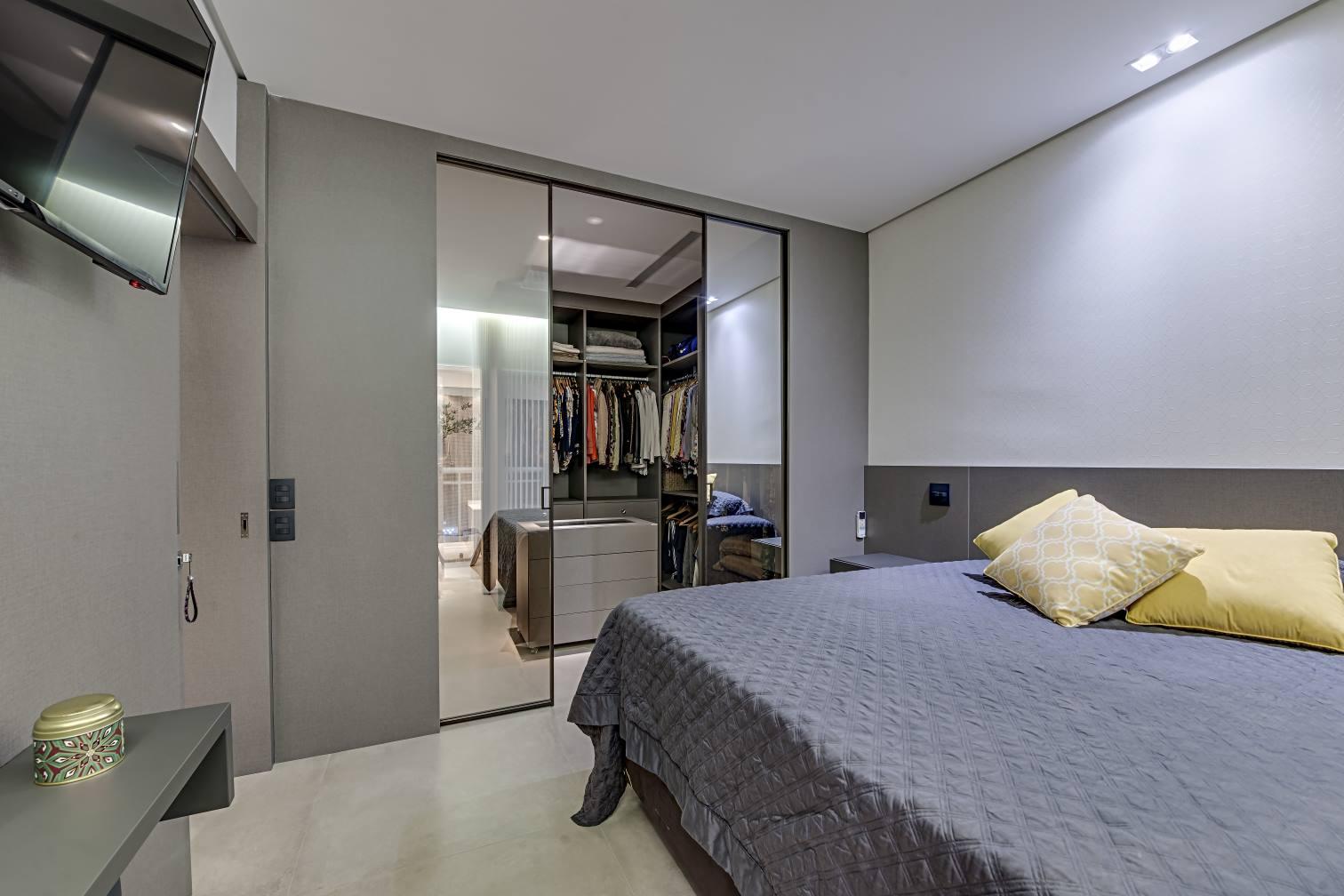 O eixo central do closet sempre pede um pufe ou um móvel para os acessórios