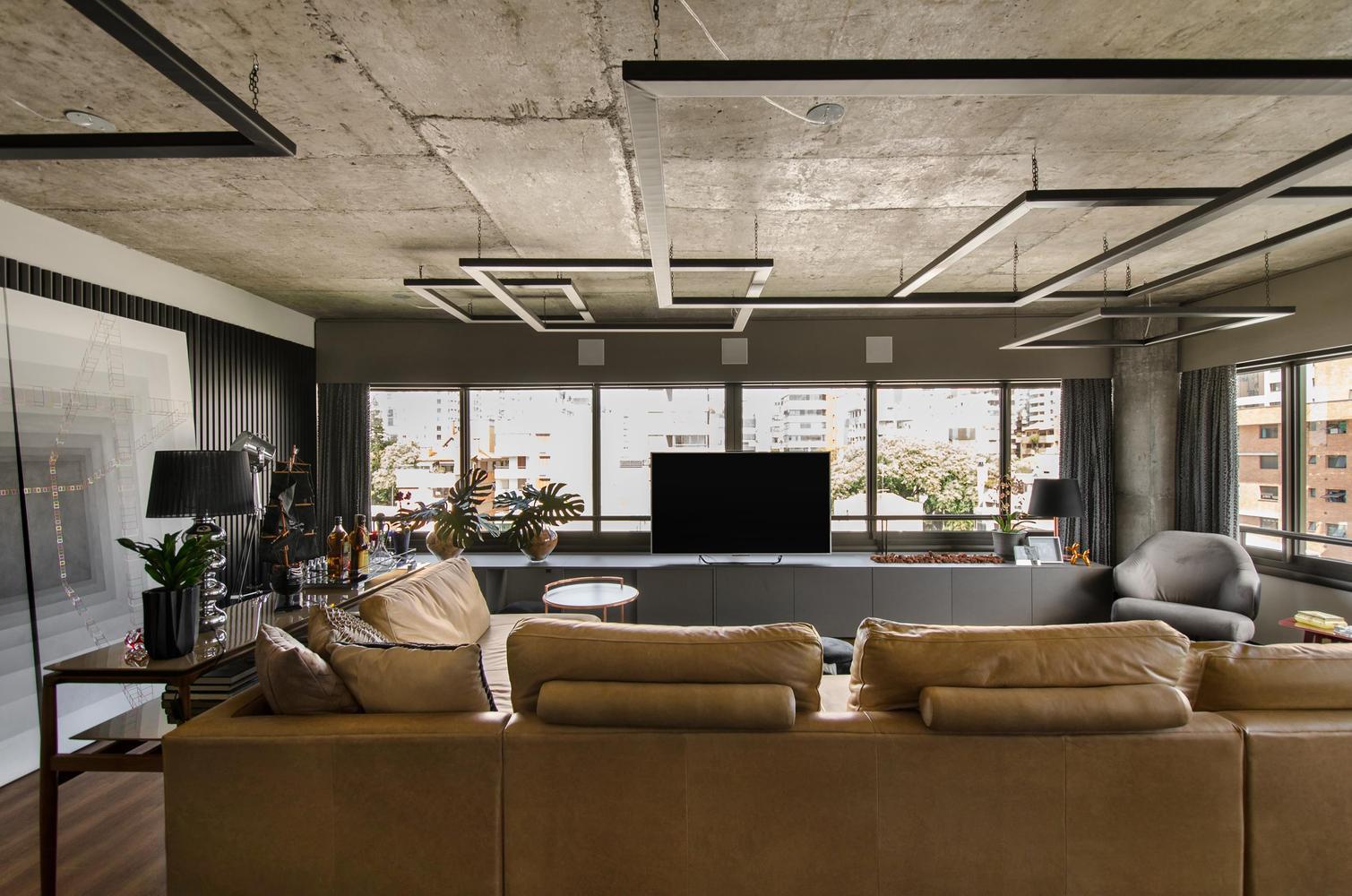 A pegada industrial deixa a sala de TV moderna e arrojada.