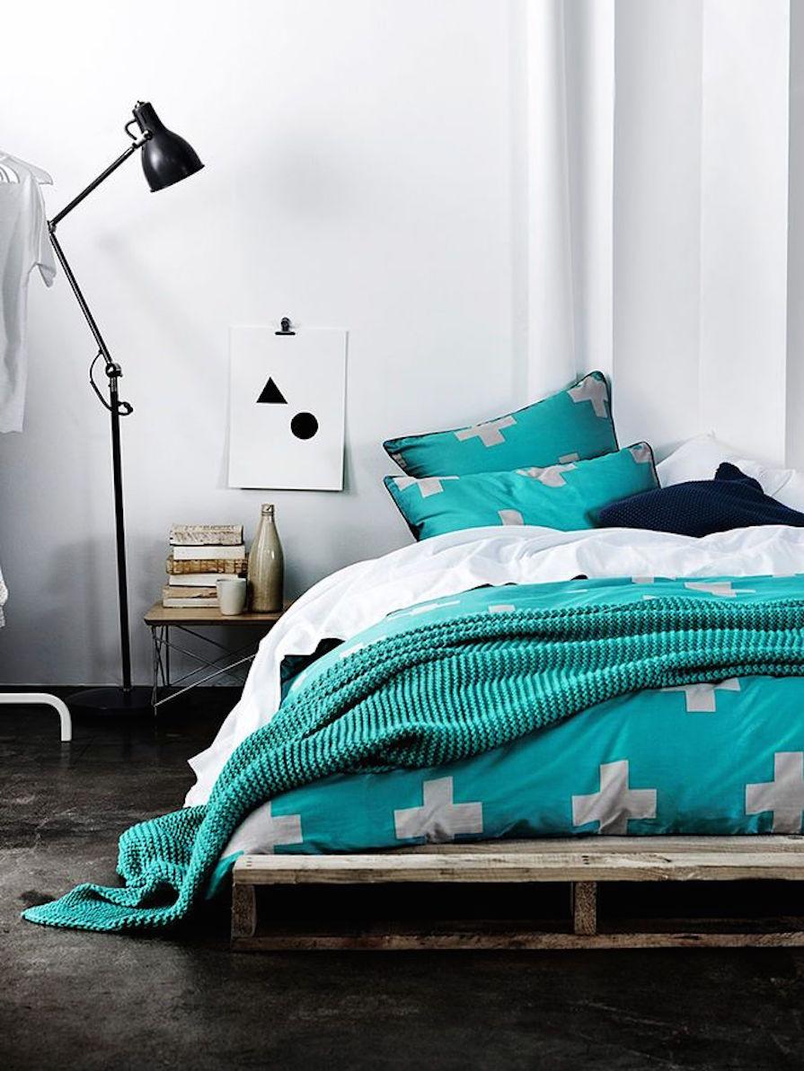 Escolha uma roupa de cama marcante para contrastar com a madeira do pallet