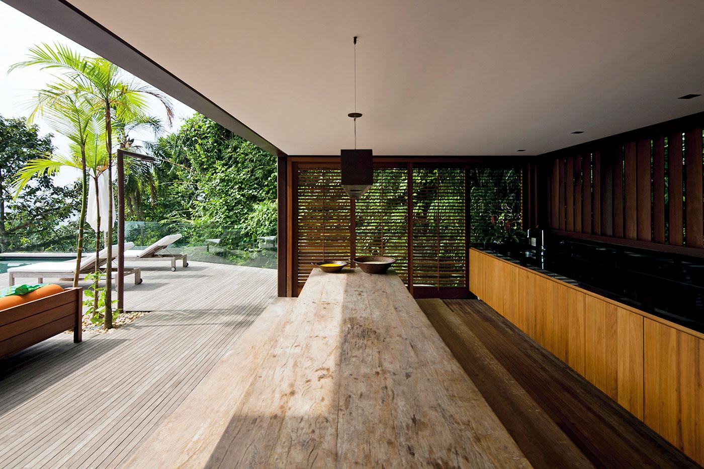 Cozinha em área externa com bancada de madeira, brises e mesa rústica extensa