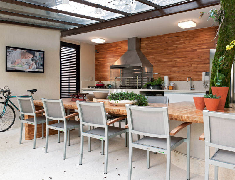 Cozinha externa com churrasqueira, bancada de madeira, pia e geladeira