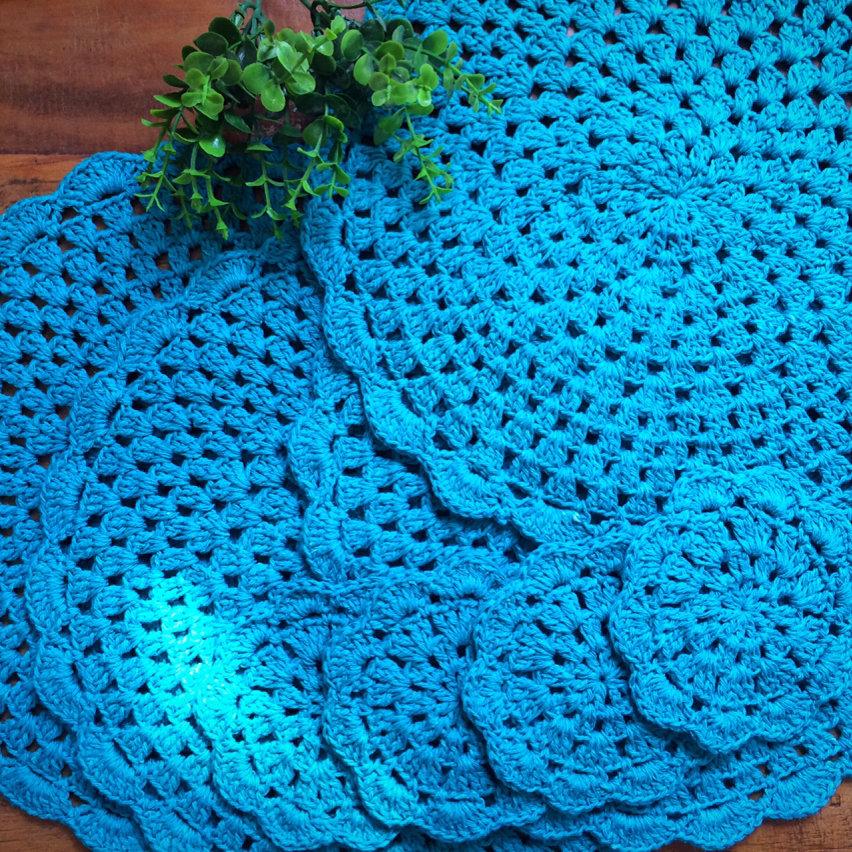 Opção de sousplat de crochê azul com pequenos porta copos.