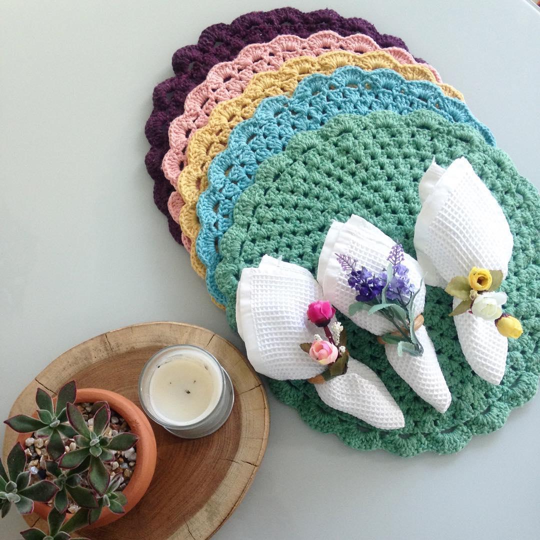 Um jogo multicolorido de sousplats de crochê com roxo, rosa, amarelo, azul e verde água.
