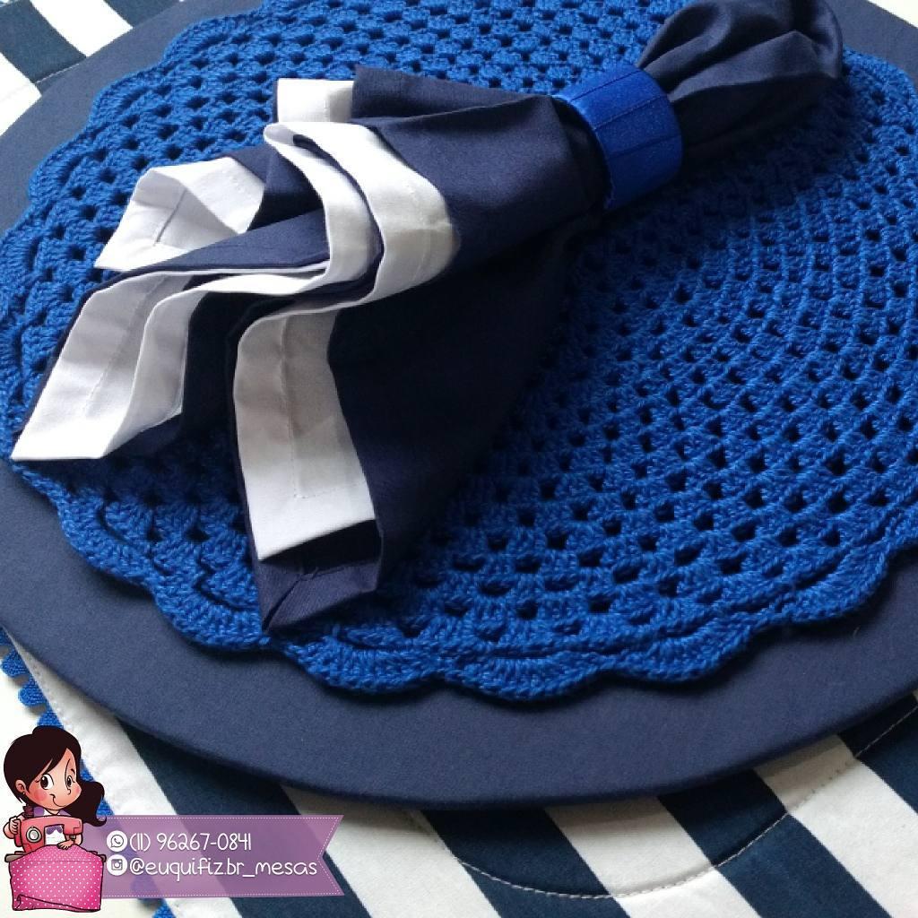 Sousplat de crochê azul sobre base para o prato e guardanapo que combina com o jogo.