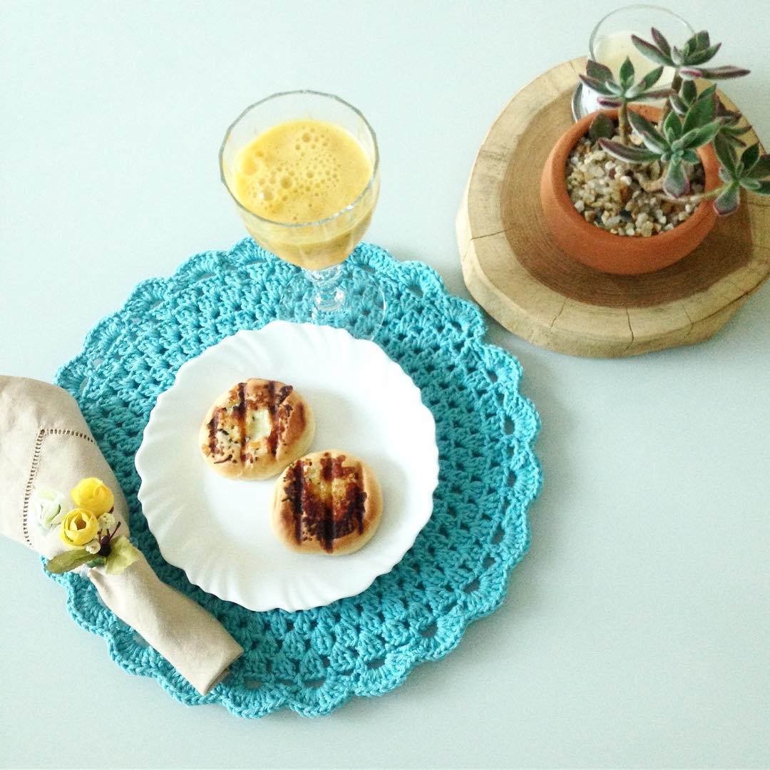 Sousplat de crochê azul para a mesa de jantar combinado com vaso.