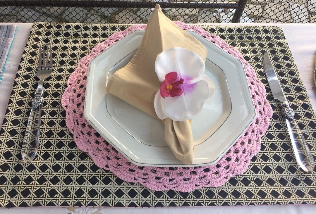 Modelo de sousplat de crochê rosa para a mesa de jantar.