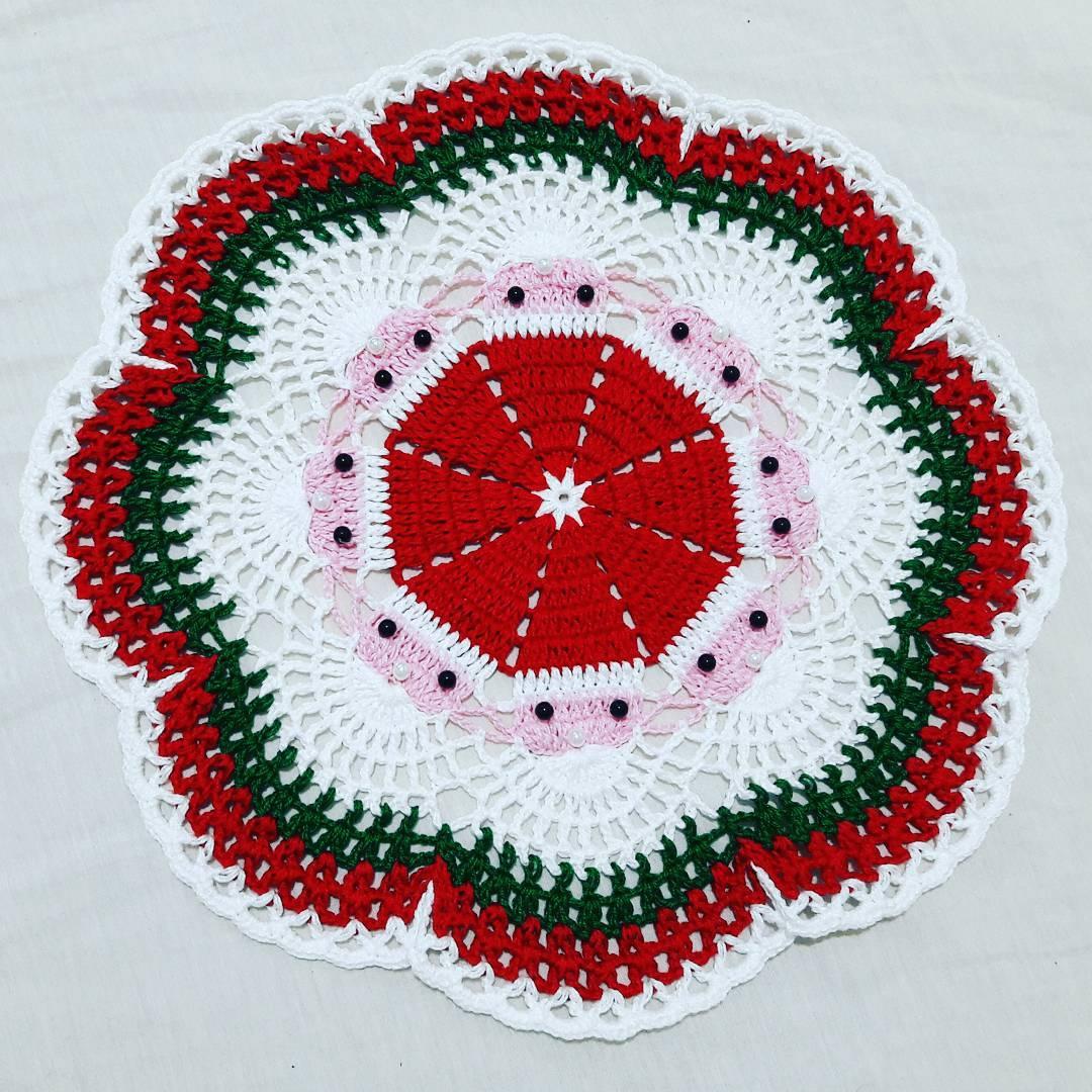 Outro modelo de sousplat de crochê natalino com pérolas decorativas.