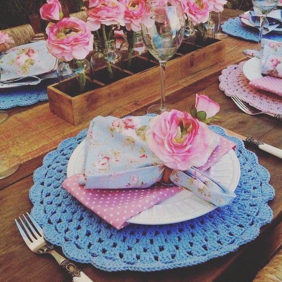 Modelo de sousplat de crochê azul em uma linda mesa com flores.