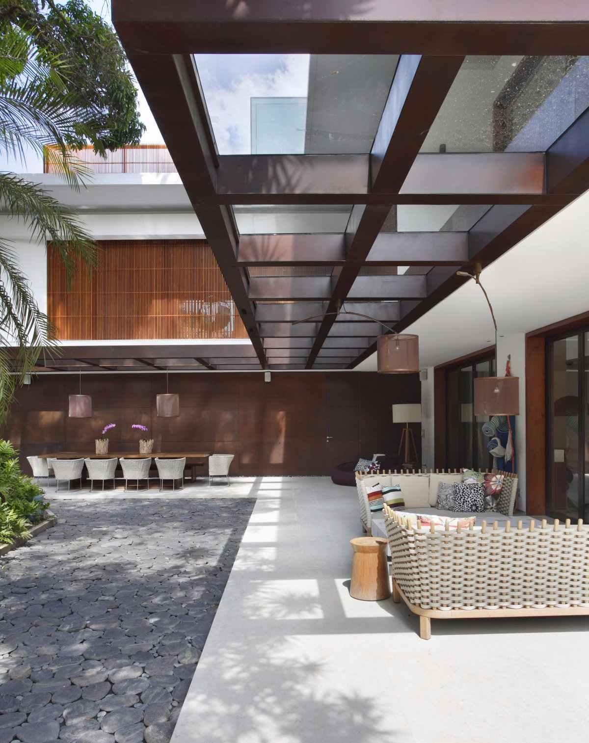 O telhado de vidro define a área de circulação externa da casa