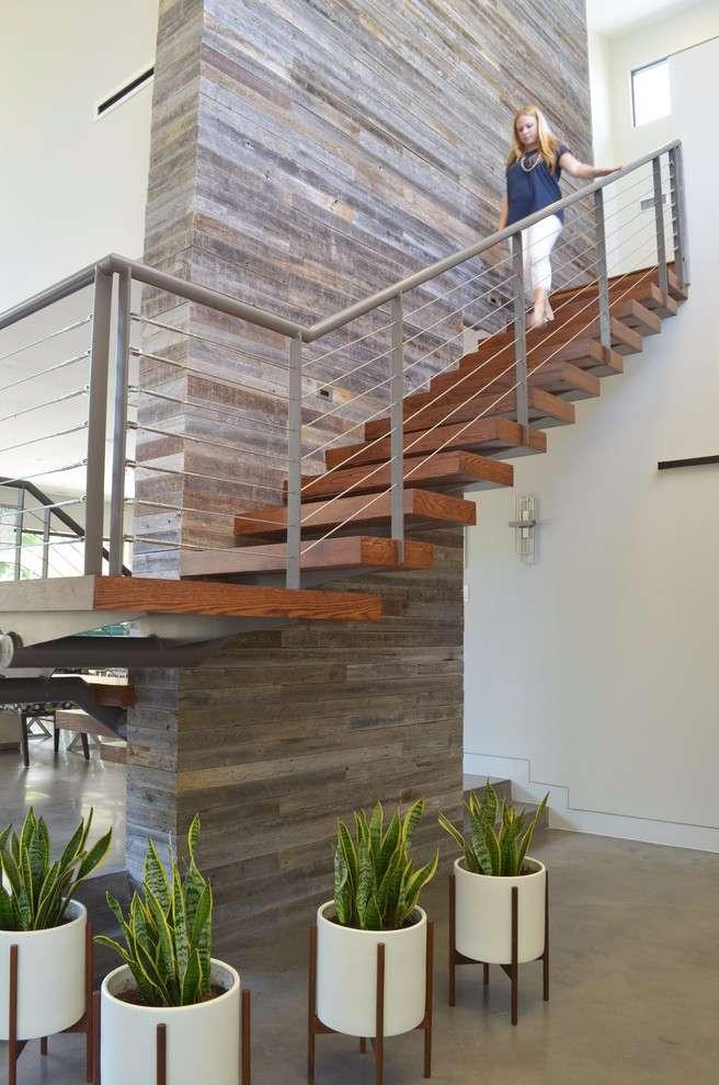 Coluna e parede com o mesmo acabamento, do piso inferior até a parte superior com escada.
