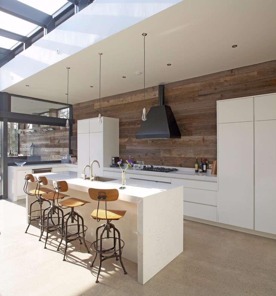 Esta proposta cria um contraste com a decoração clean utilizando do revestimento de madeira na parede da cozinha.