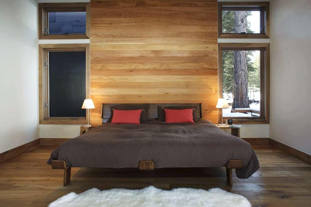 Esta proposta aplica uma madeira mais clara na parede da cabeceira da cama de casal.