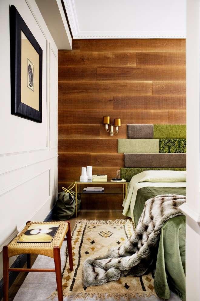 Detalhe para o acabamento da cabeceira em tecido que segue o formato e tamanho das placas de madeira da parede.