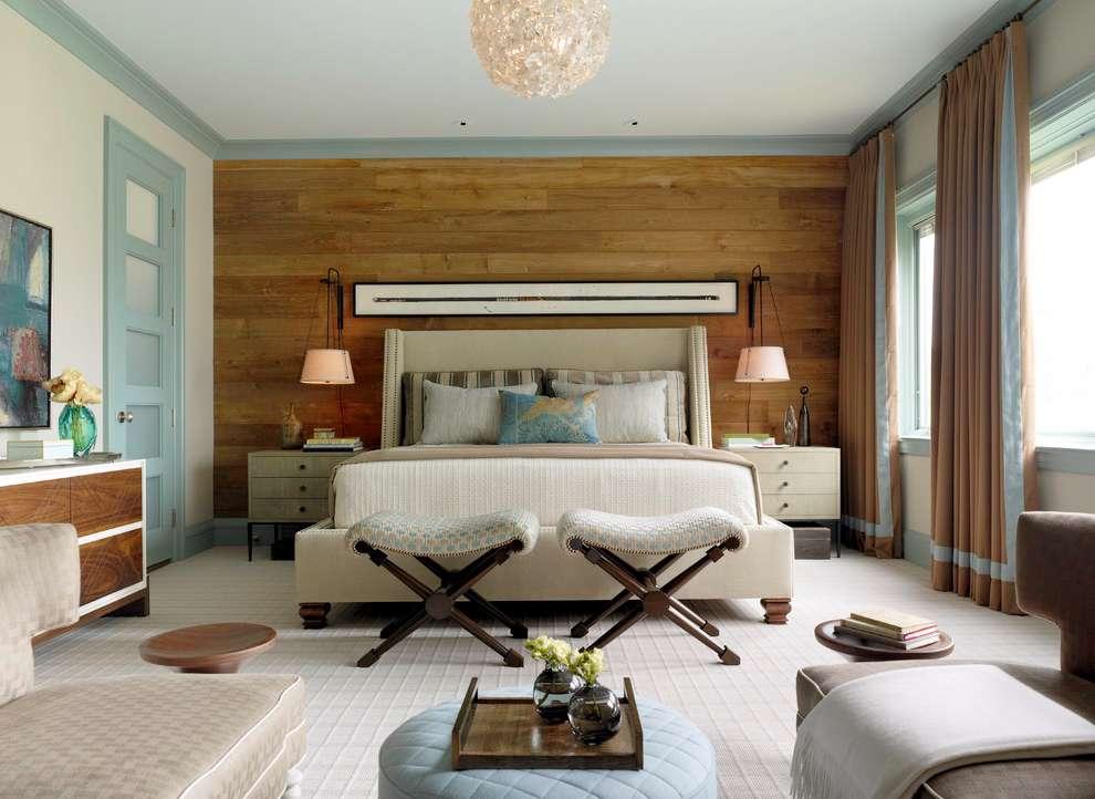 Um quarto de luxo de casal que combina o acabamento da parede de madeira com a cômoda.