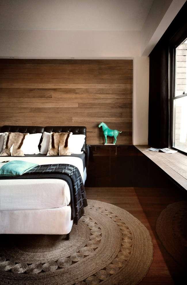Em continuidade com o piso, a parede de madeira complementa a decoração do quarto de casal.