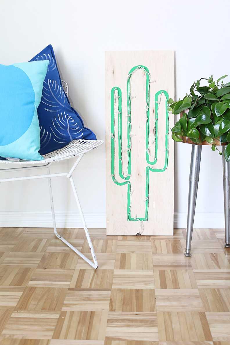 Painel de madeira com cactus e luz de pisca pisca