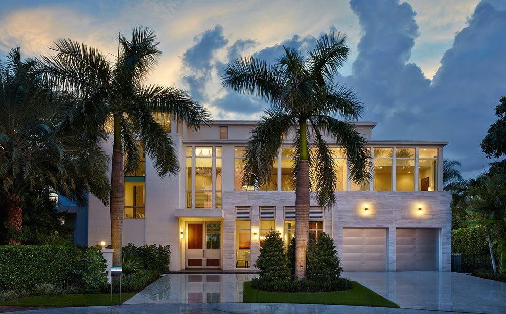 Casa grande com coqueiros na frente