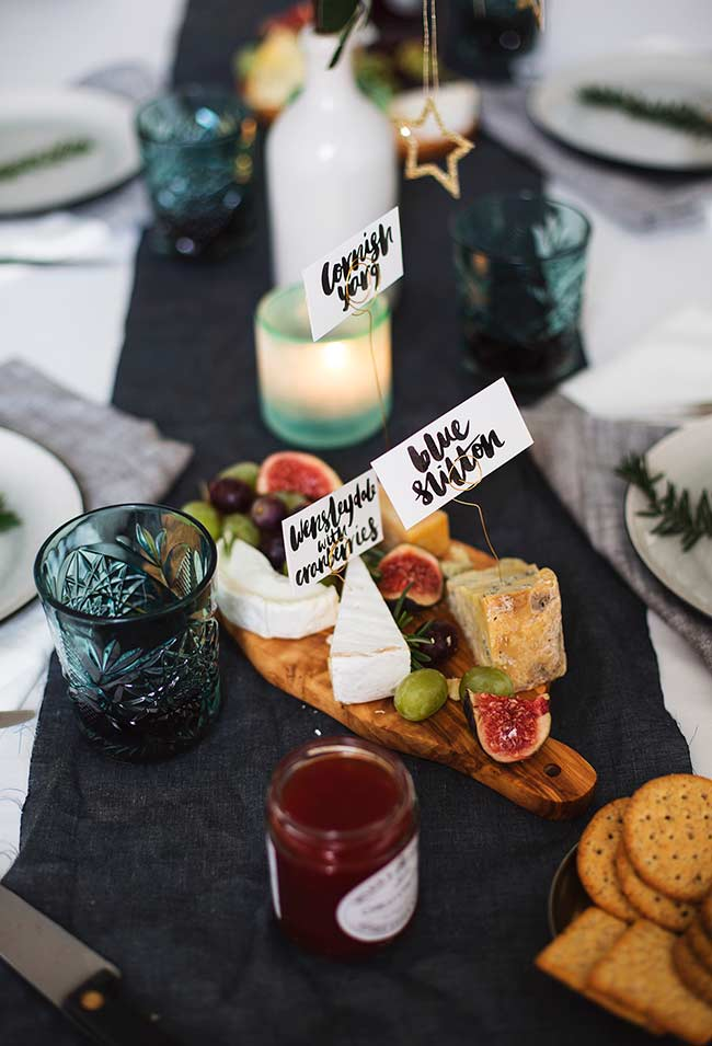 Contraste entre centro de mesa escuro e detalhes decorativos em cores claras.
