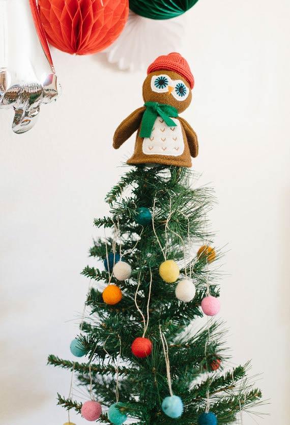 Uma corujinha protegida do frio no topo da árvore