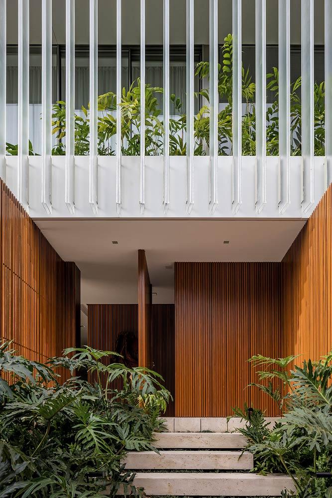 Entrada de casa com caminho de concreto e inspiração tropical
