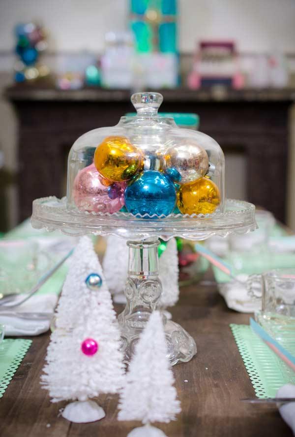 Bolinhas de Natal coloridas na redoma de vidro no centro de mesa
