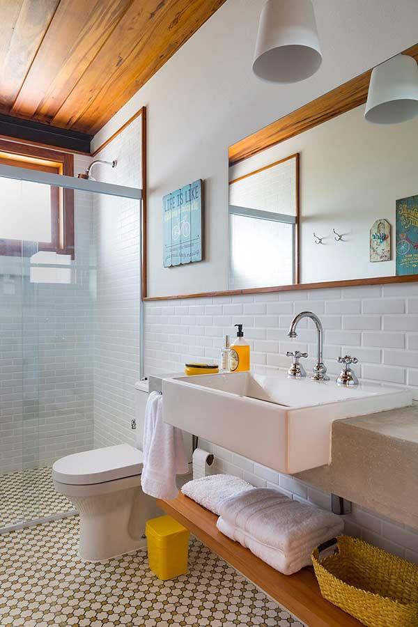 Banheiro com azulejos brancos na parede