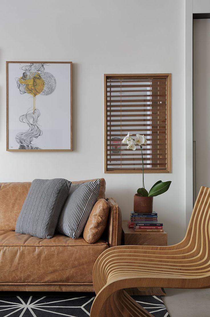 Almofadas com tons neutros em sofá de couro marrom