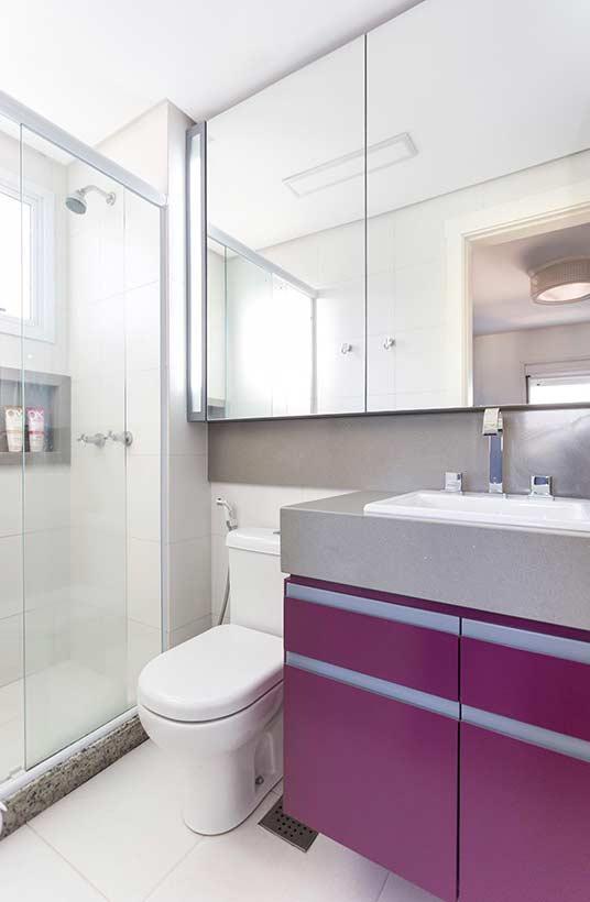 Banheiro com contraste entre a cerâmica branca do revestimento de parede e piso com materiais e objetos