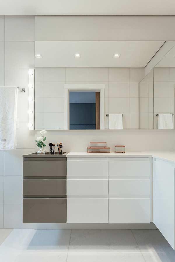 Banheiro com cerâmica branca e bancada com decoração diferenciada