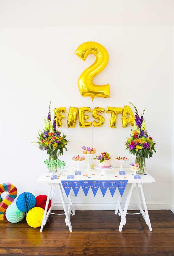 Arranjos coloridos em mesa de festa