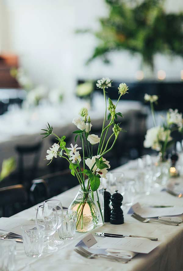 Arranjo de flores para mesa com a presença forte do verde no caule