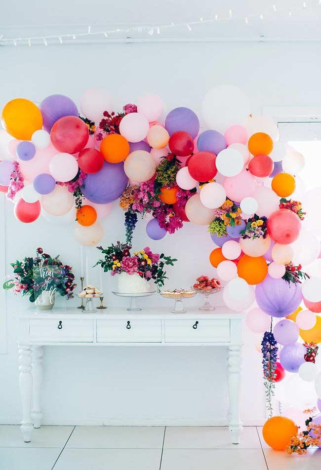 Arranjos de flores em decoração com bexigas para festa