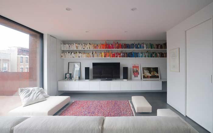 Sala de TV com prateleiras no topo da parede: aqui a escolha se dá pela organização por cores.