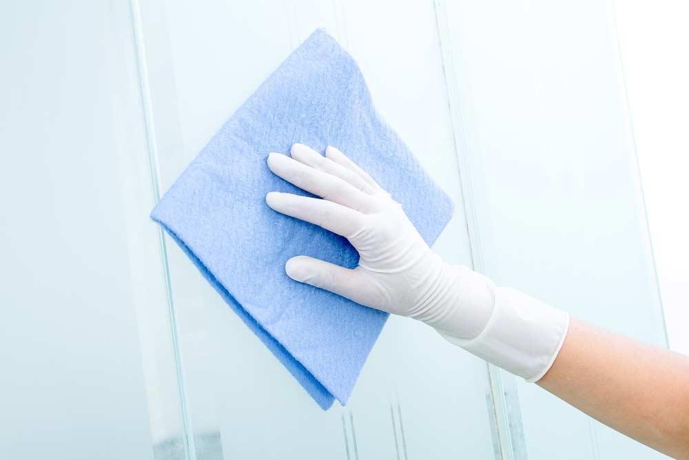Mão limpando vidro