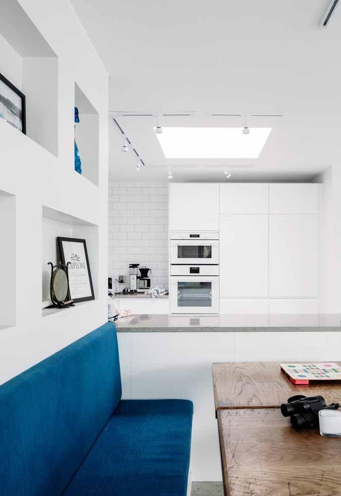 O banco azul faz um contraste super elegante nesta cozinha branca.