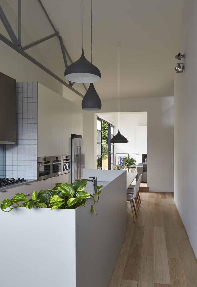 Cozinha moderna branca com ilha central e mesa